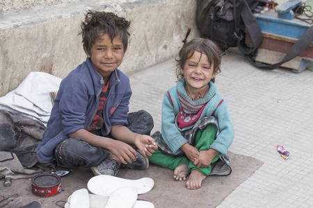 begs: LEH, INDIA - SEPTEMBER 08, 2014 : An unidentified beggar girl and boy begs for money from a passerby in Leh. Poverty is a major issue in India Editorial