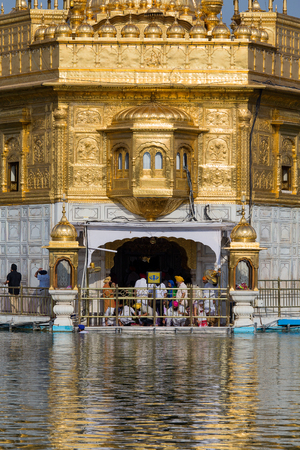 amritsar: AMRITSAR, INDIA - SEPTEMBER 29, 2014: Unidentified Sikhs and indian people visiting the Golden Temple in Amritsar, Punjab, India. Sikh pilgrims travel from all over India to pray at this holy site.