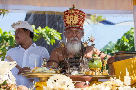 19 year old: UBUD, BALI, INDONESIA - MARCH 19, 2015 : Unidentified Indonesian people celebrate Balinese New Year and the arrival of spring. Old Brahmin conducts religious ritual on the beach Ketewel