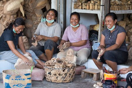 woodcarving: UBUD, BALI, INDONESIA - MARCH 23, 2015 : Unidentified women are making wooden souvenirs for tourists. Woodcarving is a traditional handicraft in Bali Editorial