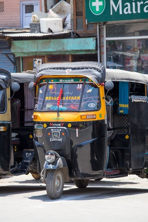 auto rickshaw: SRINAGAR, INDIA - JULE 03, 2015: Auto rickshaw taxis on a road in Kashmir, India. These iconic taxis have recently been fitted with CNG powered engines in an effort to reduce pollution