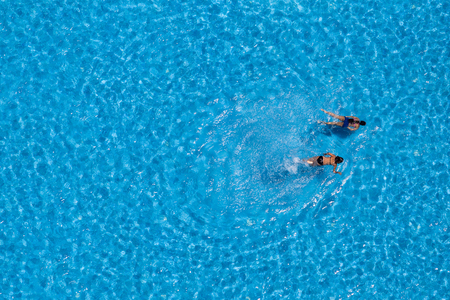 Couple girls swim in the pool at the hotel. View from above.