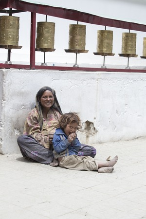 impoverished: LEH, INDIA - JUNE 24, 2015: Unknown beggar woman with a child begging near a Buddhist temple in Leh, Ladakh. Poverty is a major issue in India