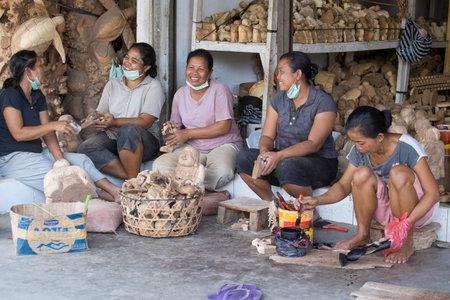 tallado en madera: Ubud, Bali, Indonesia - 23 de marzo 2015: las mujeres no identificados est�n haciendo recuerdos de madera para los turistas. Alebrije es una artesan�a tradicional en Bali