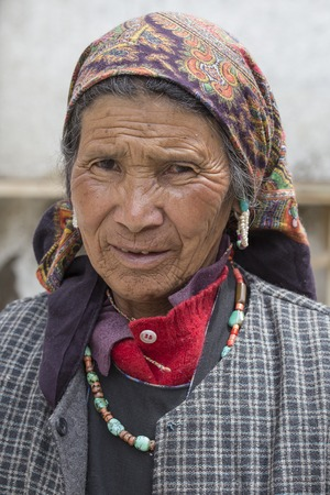 underprivileged: LEH, INDIA - JUNE 24, 2015: Unknown beggar woman begging on the street in Leh, Ladakh. Poverty is a major issue in India