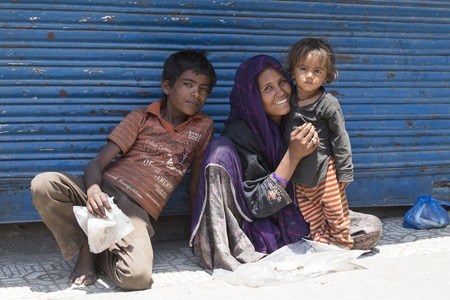 SRINAGAR, INDIA - JULY 03, 2015: Unknown beggar woman and children begging near a Buddhist temple in Srinagar. Poverty is a major issue in India Editorial