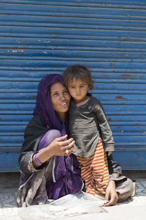 underprivileged: SRINAGAR, INDIA - JULY 03, 2015: Unknown beggar woman and children begging near a Buddhist temple in Srinagar. Poverty is a major issue in India Editoriali
