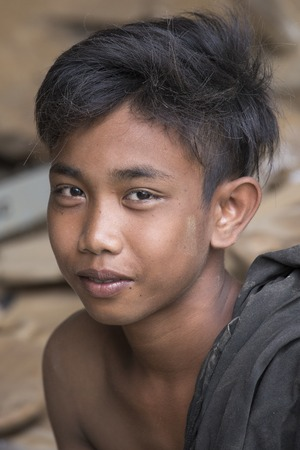 unknown age: UBUD, BALI, INDONESIA - MARCH 29, 2015 : Portrait of unknown young guy working in carpentry shop. Teens in Indonesia started his career very early age Editorial