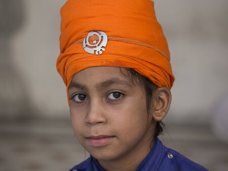 amritsar: AMRITSAR, INDIA - SEPTEMBER 27, 2014: Unidentified young Sikh boy visiting the Golden Temple in Amritsar, Punjab, India. Sikh pilgrims travel from all over India to pray at this holy site.