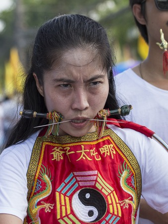 PHUKET, THAILAND - OCT 17, 2015: Chinese thai girl possessed by his god walks with his mouth pierced in Vegetarian Festival at Phuket Town. Festival is a famous annual also known as Nine Emperor Gods