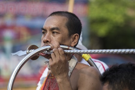 PHUKET, THAILAND - OCT 17, 2015: Chinese thai monk possessed by his god walks with his mouth pierced in Vegetarian Festival at Phuket Town. Festival is a famous annual also known as Nine Emperor Gods Editorial