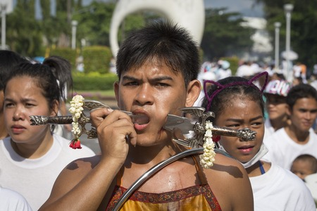 thai monk: PHUKET, THAILAND - OCT 17, 2015: Chinese thai monk possessed by his god walks with his mouth pierced in Vegetarian Festival at Phuket Town. Festival is a famous annual also known as Nine Emperor Gods Editorial