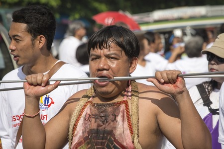 masochism: PHUKET, THAILAND - OCT 17, 2015: Chinese thai monk possessed by his god walks with his mouth pierced in Vegetarian Festival at Phuket Town. Festival is a famous annual also known as Nine Emperor Gods Editorial