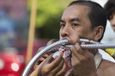 possessed: PHUKET, THAILAND - OCT 17, 2015: Chinese thai monk possessed by his god walks with his mouth pierced in Vegetarian Festival at Phuket Town. Festival is a famous annual also known as Nine Emperor Gods Editorial