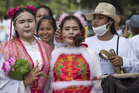 masochism: PHUKET, THAILAND - OCT 17, 2015: Chinese thai girl possessed by his god walks with his mouth pierced in Vegetarian Festival at Phuket Town. Festival is a famous annual also known as Nine Emperor Gods