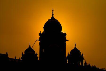 amritsar: Silhouette Amritsar Golden Temple in India at sunset Stock Photo