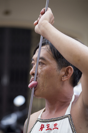 PHUKET, THAILAND - OCT 18, 2015: Chinese thai monk possessed by his god walks with his mouth pierced in Vegetarian Festival at Phuket Town. Festival is a famous annual also known as Nine Emperor Gods