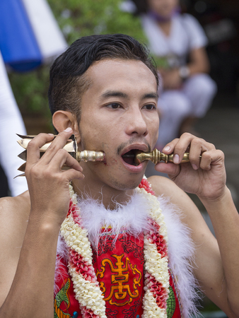 possessed: PHUKET, THAILAND - OCT 18, 2015: Chinese thai monk possessed by his god walks with his mouth pierced in Vegetarian Festival at Phuket Town. Festival is a famous annual also known as Nine Emperor Gods