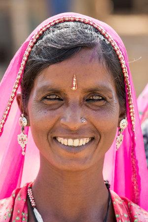 camello: Pushkar, India - 28 de octubre 2014: una mujer no identificada observa mientras ella asiste a la anual Pushkar Camel Mela. Esta feria es la mayor feria de comercio de camellos en el mundo. Editorial