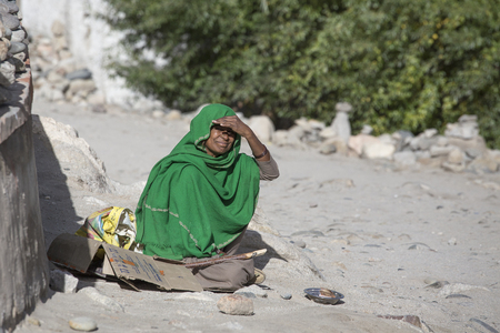 begs: LEH, INDIA - SEPTEMBER 08, 2014: Unknown poor woman begs for money from a passerby on the street in Leh, Ladakh. Poverty is a major issue in India Editorial