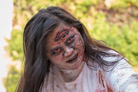 face zombie: BANGKOK,THAILAND - JANUARY 8, 2015: Unknown Thai girl participates in  FOX Thai The Walking Dead Season 5 Marathon , dressed as zombies Editorial