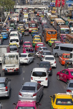 co2 emissions: BANGKOK, THAILAND - JANUARY 22, 2015: Traffic moves slowly along a busy road in Bangkok, Thailand. Annually an estimated 150,000 new cars join the already heavily congested streets of Bangkok.