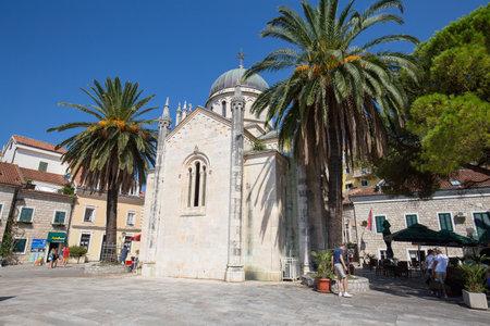 archangel: HERCEG NOVI, MONTENEGRO - SEPTEMBER 13, 2015: Unidentified tourists walk on the square Duke Stefan, Bellavista near Orthodox Church of Archangel Michael in Herceg Novi, Montenegro