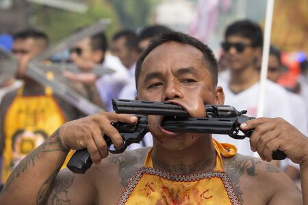 god: PHUKET, THAILAND - OCT 18, 2015: Chinese thai monk possessed by his god walks with his mouth pierced in Vegetarian Festival at Phuket Town. Festival is a famous annual also known as Nine Emperor Gods