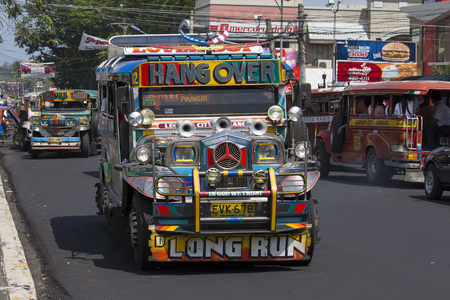inexpensive: LEGAZPI, PHILIPPINES - MARCH 18, 2014: Jeepneys passing, Filipino inexpensive bus service. Jeepneys are the most popular means of public transportation in the Philippines. Editorial