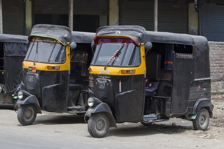 auto rickshaw: SRINAGAR, INDIA - JULE 02, 2015: Auto rickshaw taxis on a road in Kashmir, India. These iconic taxis have recently been fitted with CNG powered engines in an effort to reduce pollution