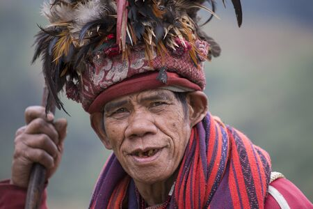 refers: BANAUE, PHILIPPINES - JANUARY 24, 2014 : Unknown old ifugao man in national dress next to rice terraces. Ifugao - the people in the Philippines. Refers to the mountain peoples. Editorial