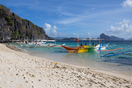 nido: EL NIDO, PHILIPPINES - JANUARY 31, 2014 : Boats waiting for tourists to travel between the islands. El Nido is one of the top tourist destinations in the world.