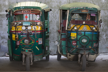 three wheeler: RISHIKESH, INDIA - OCTOBER 19, 2014 : Auto rickshaw taxis on a road. These iconic taxis have recently been fitted with CNG powered engines in an effort to reduce pollution Editorial