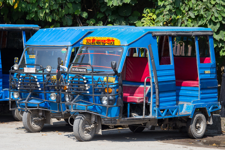 three wheeler: RISHIKESH, INDIA - OCTOBER 20, 2014 : Auto rickshaw taxis on a road. These iconic taxis have recently been fitted with CNG powered engines in an effort to reduce pollution