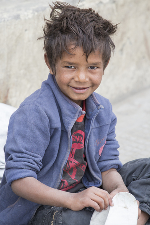 LEH, INDIA - SEPTEMBER 08 2014: Unidentified beggar boy begs for money from a passerby in Leh. Poverty is a major issue in India Editorial
