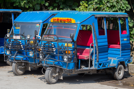 auto rickshaw: RISHIKESH, INDIA - OCTOBER 20, 2014 : Auto rickshaw taxis on a road. These iconic taxis have recently been fitted with CNG powered engines in an effort to reduce pollution