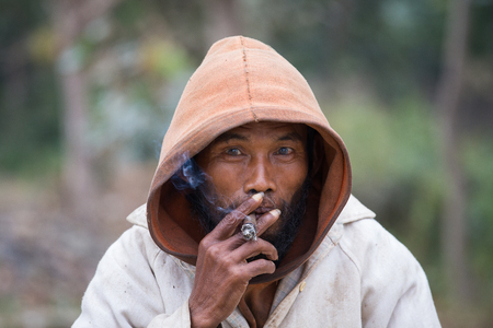 MRAUK-U, MYANMAR - JANUARY 27, 2016: Portrait of an unknown beggar who smokes a cigarette outdoors