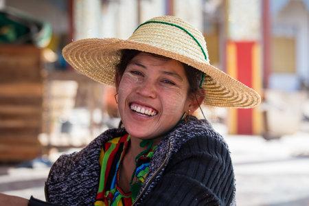 INLE LAKE, MYANMAR - JANUARY 12, 2016: Portrait burmese girl a straw hat in local market. Inle lake, Myanmar, Burma Editorial