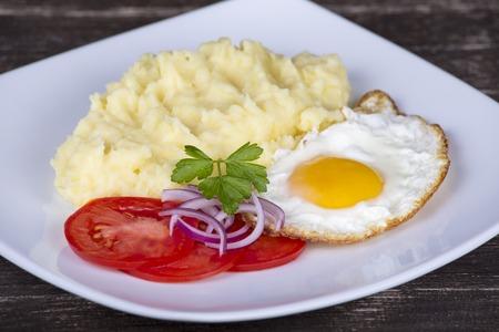 pure de papas: El puré de patatas con huevos fritos y el tomate. De cerca