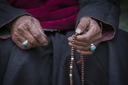 różaniec: Stara kobieta trzyma tybetański buddyjski różaniec w Hemis klasztorze, Ladakh, Indie. Ręka i różaniec, bliska