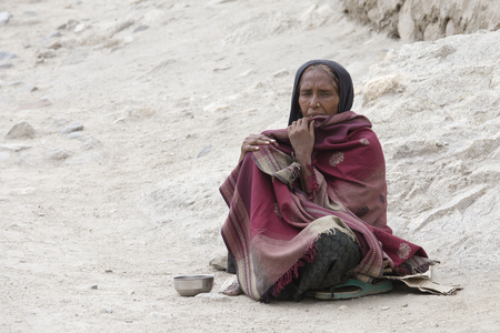 impoverished: LEH, INDIA - JUNE 24, 2015: Unknown poor woman begs for money from a passerby on the street in Leh, Ladakh. Poverty is a major issue in India