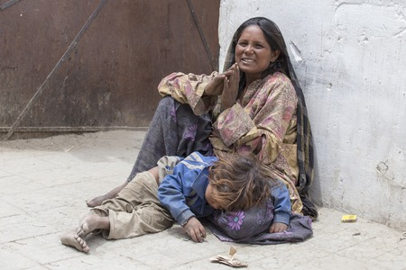 slum: LEH, INDIA - JUNE 24, 2015: Unknown beggar woman with a child begging near a Buddhist temple in Leh, Ladakh. Poverty is a major issue in India