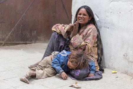 LEH, INDIA - 24 de junio, 2015: mendiga desconocido con un niño mendigando cerca de un templo budista en Leh, Ladakh. La pobreza es un problema importante en la India