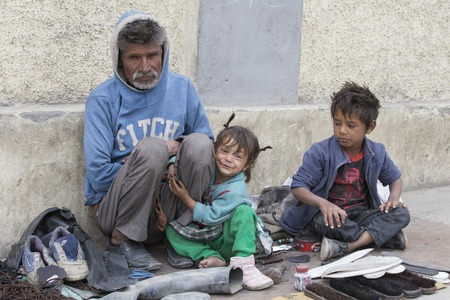 begs: LEH, INDIA - SEPTEMBER 08 2014: An unidentified beggar family begs for money from a passerby in Leh. Poverty is a major issue in India