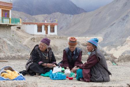 dance time: LAMAYURU, INDIA - JUNE 14, 2015: Unidentified buddhist old women during mystical mask dancing Tsam mystery dance in time of Yuru Kabgyat Buddhist festival at Lamayuru Gompa, Ladakh, North India