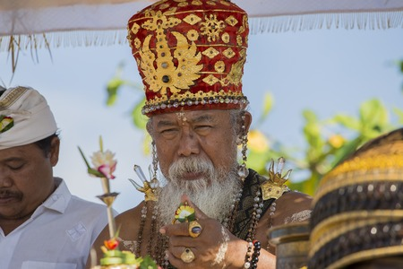 processions: UBUD, BALI, INDONESIA - MARCH 19, 2015 : Unidentified Indonesian people celebrate Balinese New Year and the arrival of spring. Old Brahmin conducts religious ritual on the beach Ketewel