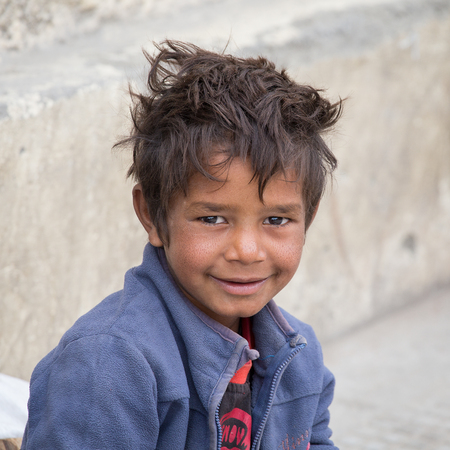 begs: LEH, INDIA - SEPTEMBER 08 2014: Unidentified beggar boy begs for money from a passerby in Leh. Poverty is a major issue in India Editorial