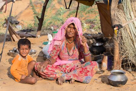 attended: PUSHKAR, INDIA - OCTOBER 27, 2014: Unidentified woman and child at the attended the annual Pushkar Camel Mela. This fair is the largest camel trading fair in the world.