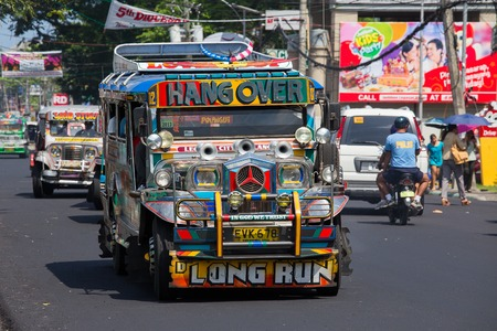 means of transportation: LEGAZPI, PHILIPPINES - MARCH 18, 2014: Jeepneys passing, Filipino inexpensive bus service. Jeepneys are the most popular means of public transportation in the Philippines. Editorial