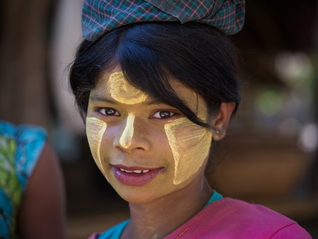 MRAUK-U, MYANMAR - JANUARY 27, 2016: Unidentified young Myanmar girl with thanaka on her smile face is happiness. Thanaka is a yellowish-white cosmetic paste made from ground bark. Editorial